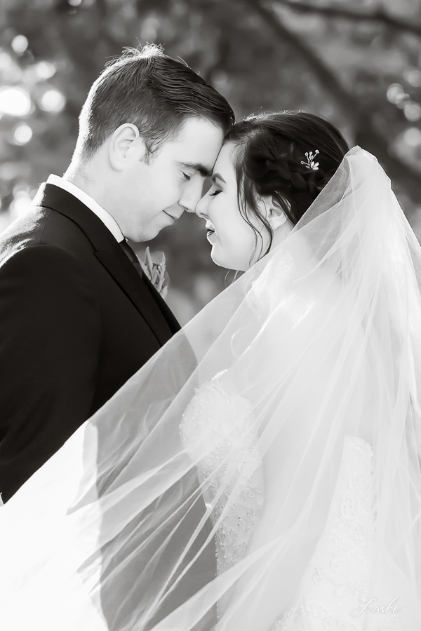 The grooms leans towards his bride and rests his head on her head as they both soak in the moment, eyes closed.